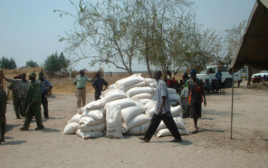 Villagers carrying bags of maize.