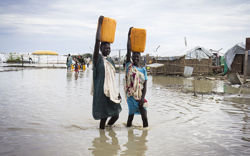 Women wade through contaminated flood water at the displacement camp on the UN base in Bentiu