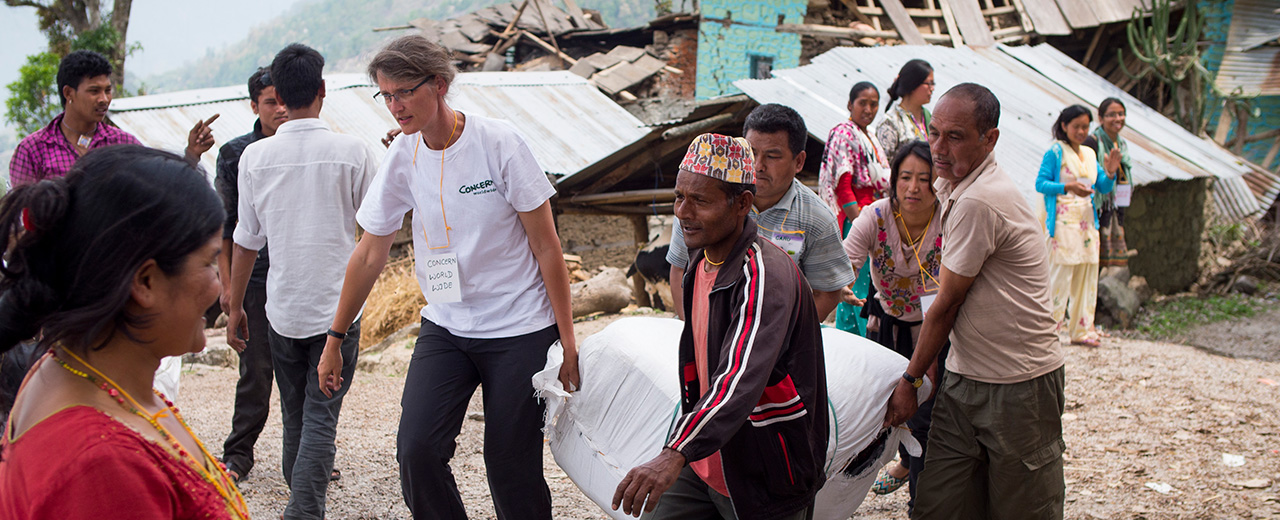 Regine Kopplow of Concern Worldwide helps villagers at a distribution of emergency shelter