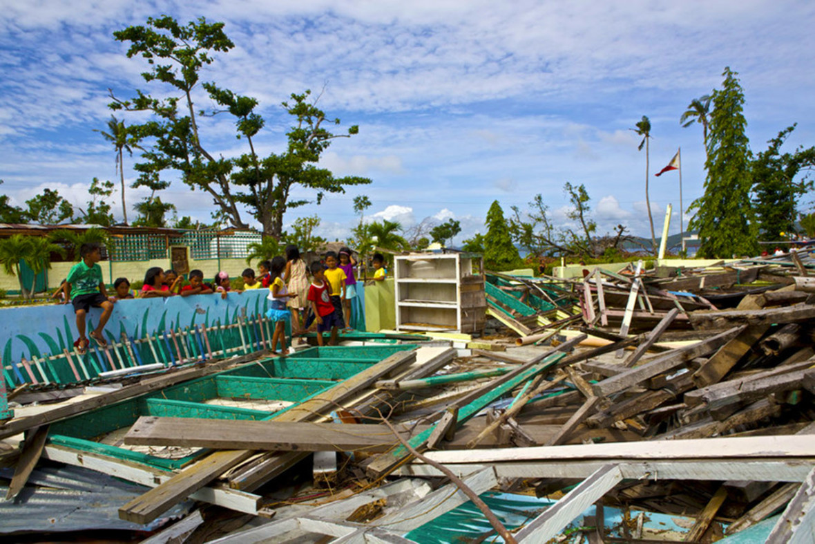 School kids look at their destroyed classroom