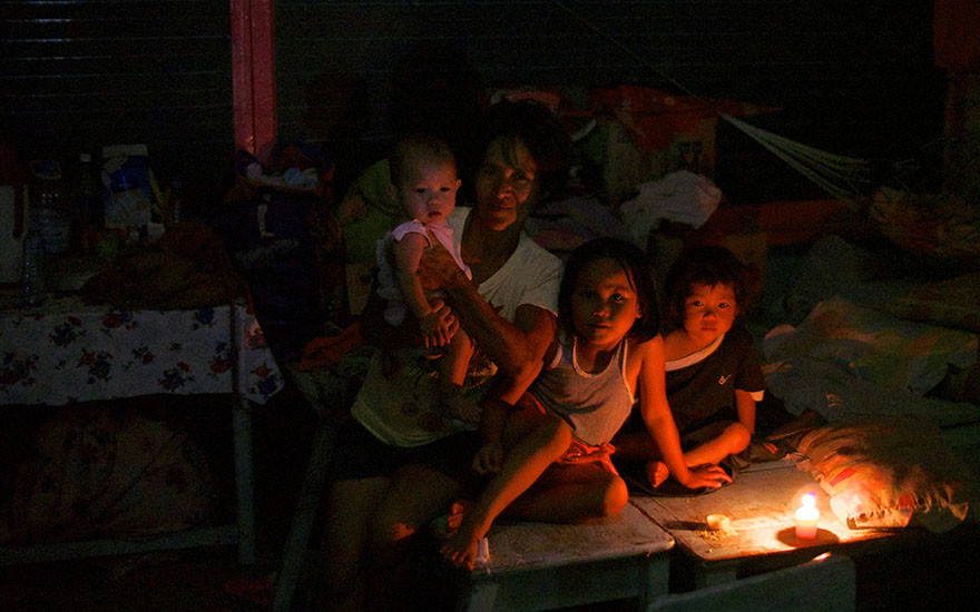 Rowena Arjona and three of her eight children huddle by candlelight in the Concepcion Central School