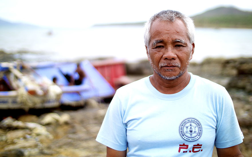 Johnny Franco stands in front of a ruined fishing boat