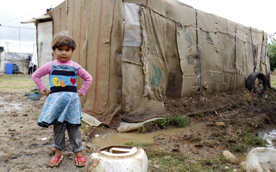 A refugee child stands in front of her home in an informal tented settlement in Bebnine