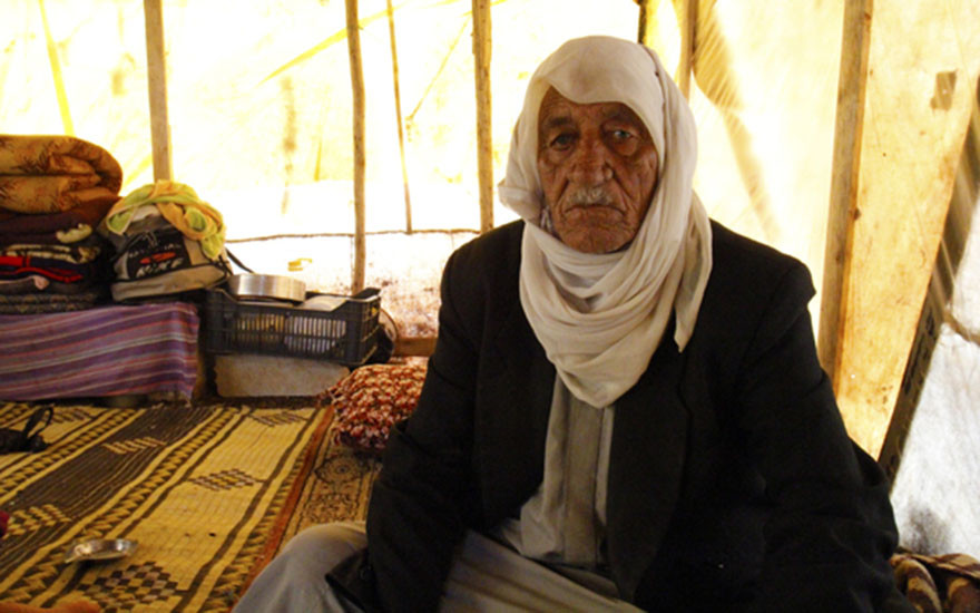 Abdul, 80, sits inside his shelter in Kwashra 3 informal tented settlement
