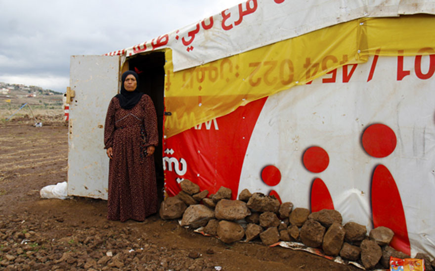 Yara stands outside of her shelter in Kwashra 1 informal tented settlement