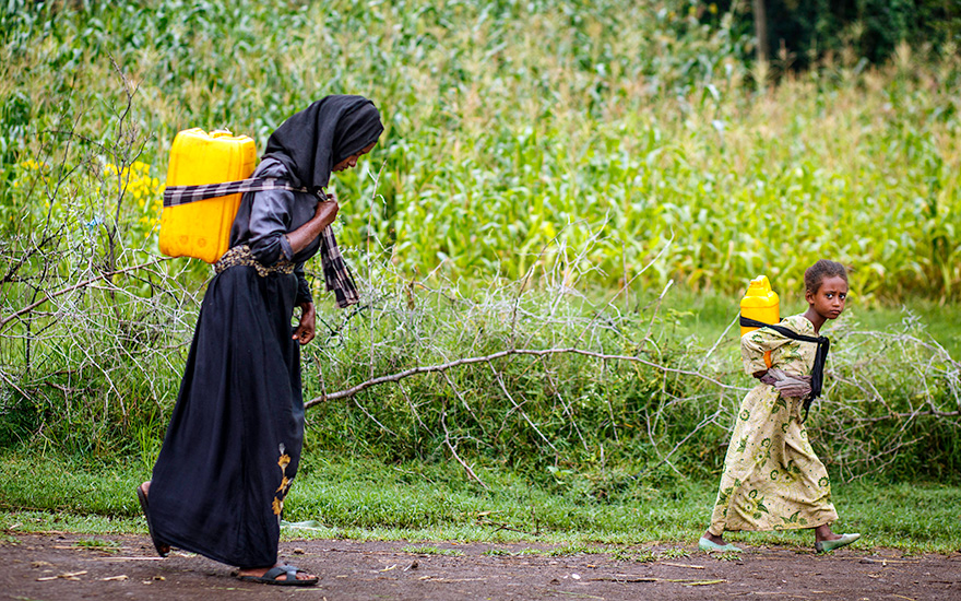 Mother and child carry water
