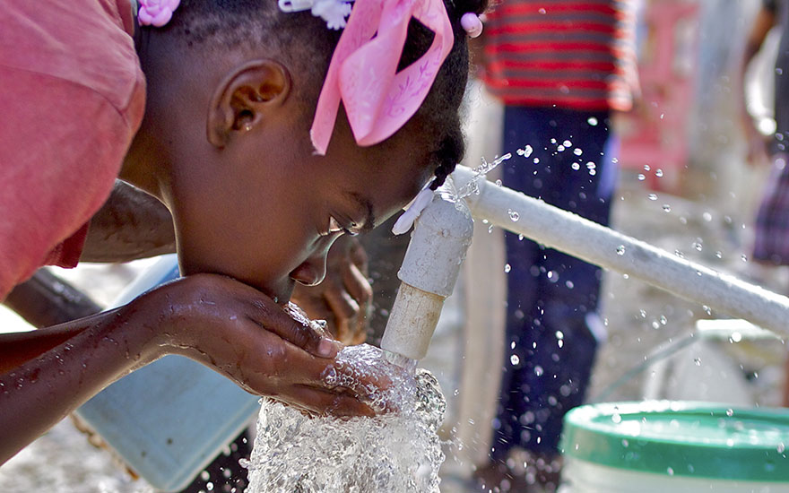 A young child drinks from a Concern water spout.