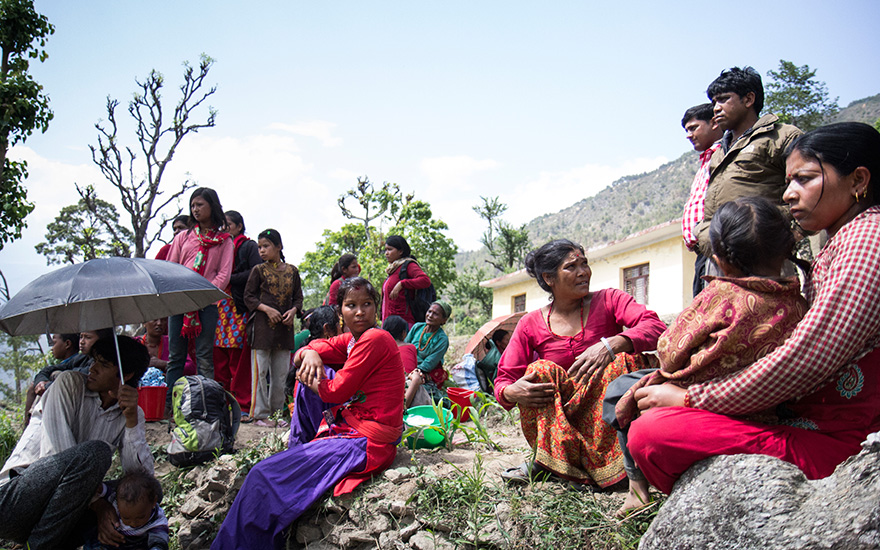 Villagers gather in an open clearing