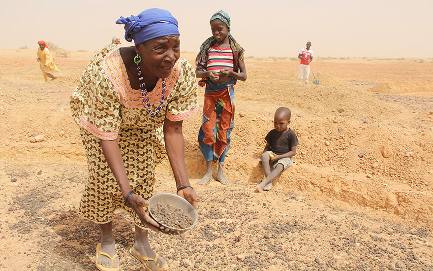 Woman working on her field being recuperated from desert