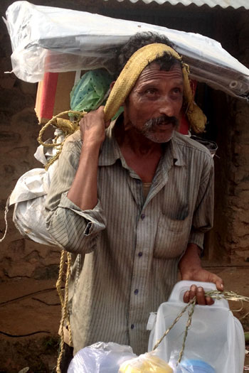 Dhan Bahadhur Bhaju carrying distribution items back to his family.