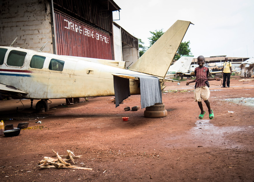 A child jumps rope beside an abandoned plane