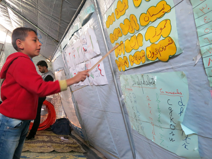 A young Syrian boy, studying both Arabic and Roman alphabets.
