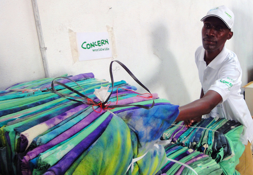 Concern staff member with supplies of blankets in Burundi