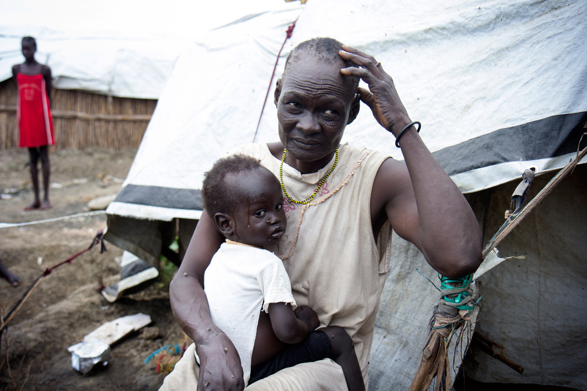 Nyalada Maluit holds her two-year-old son, Lat Machar, in front of their home in the displacement camp