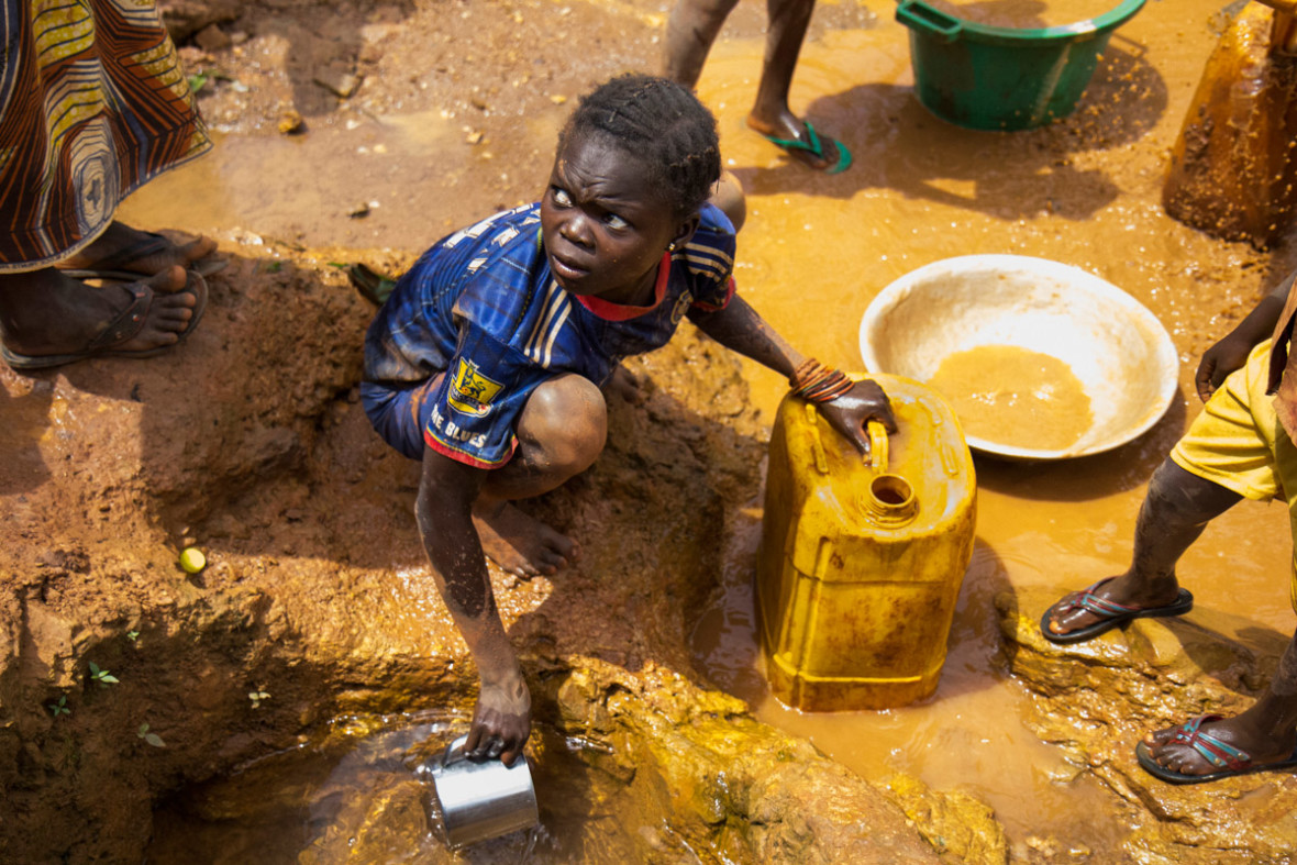 A girl collects water from a small spring