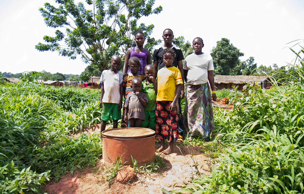 Residents of Gaga stand around a well near their homes.