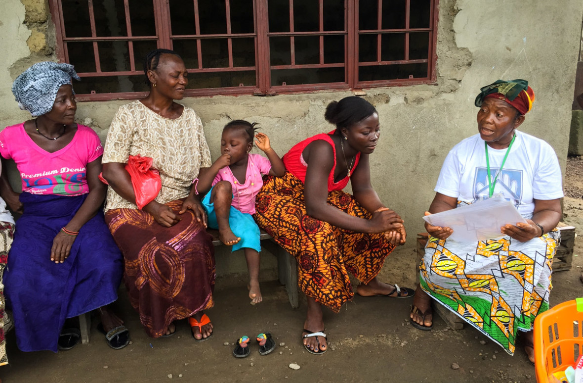 Kai Giba, a health promoter, uses pictorial cards to teach families good health practices during a home visit.