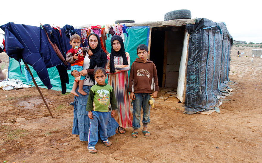 """Samar with her four children outside their makeshift shelter at Kwashra informal settlement. She, her husband, and four children fled Syria after their house was destroyed. """"I hope Syria goes back to how it was and we can go home,"""" she says. Photo: Crystal Wells"""