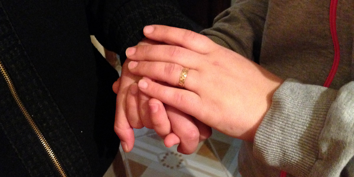 Ahmed and his wife, holding hands