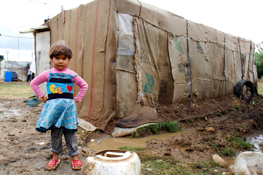 A Syrian refugee child stands in front of her home in an informal tented settlement in Bebnine, Lebanon.