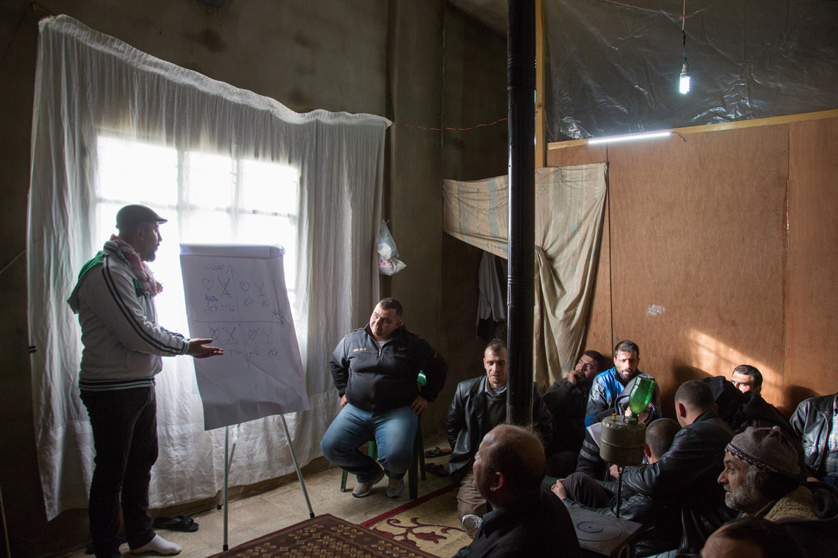 Concern Protection Field Officer Rami Fares, left, gives a session on violence to Syrian refugee men