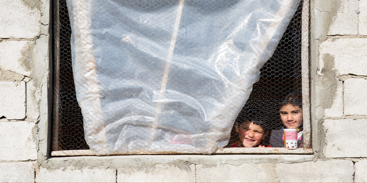 Syrian refugee Afaf, 8, and her younger brother Hani, 4, stand by the window of the kitchen in the collective shelter where they live