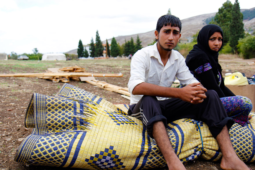 A Syrian husband and wife sit on the remains of their makeshift shelter.