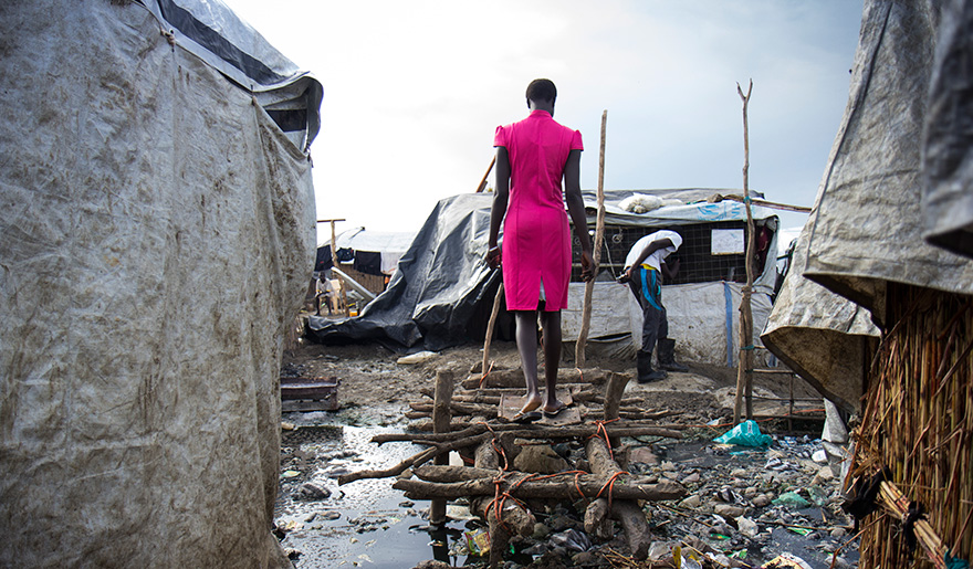A woman walks on a makeshift bridge over stagnant sewage water