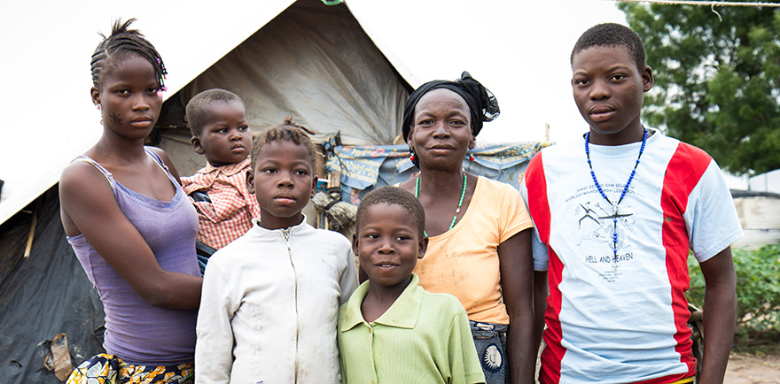 Zoumati family stands outside their makeshift shelter in the Mpoko displacement camp
