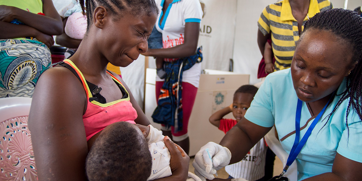 Helena Dennis, winces as her seven month old son, Abraham Clinton, gets his pneumonia vaccination.