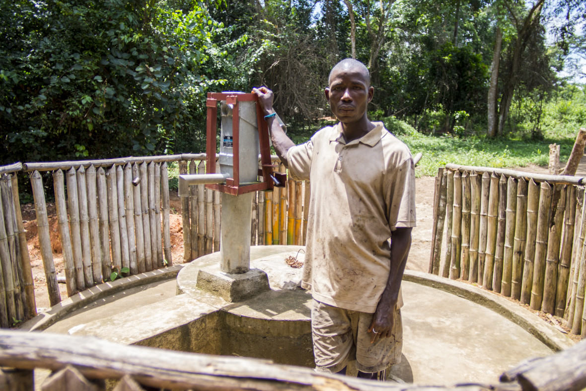 Kokulo Zaza, Towm Chief of Dokoizia village in Lofa county, Liberia, stands beside a Concern-installed water pump.