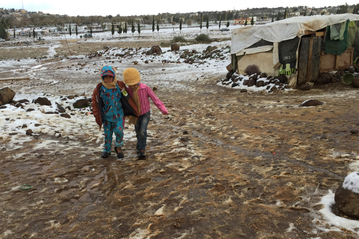 Syrian refugee children try to make their way through the snow and slurry