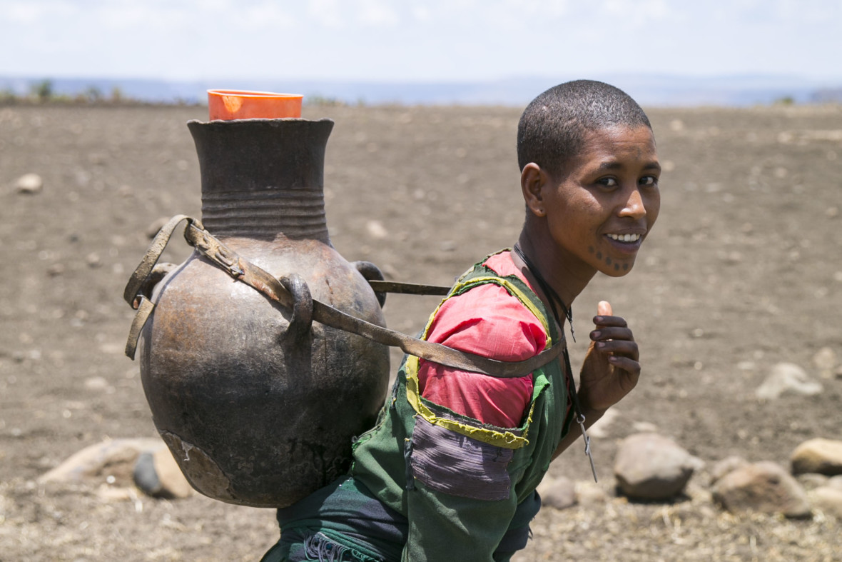 A woman walks home with water she's collected