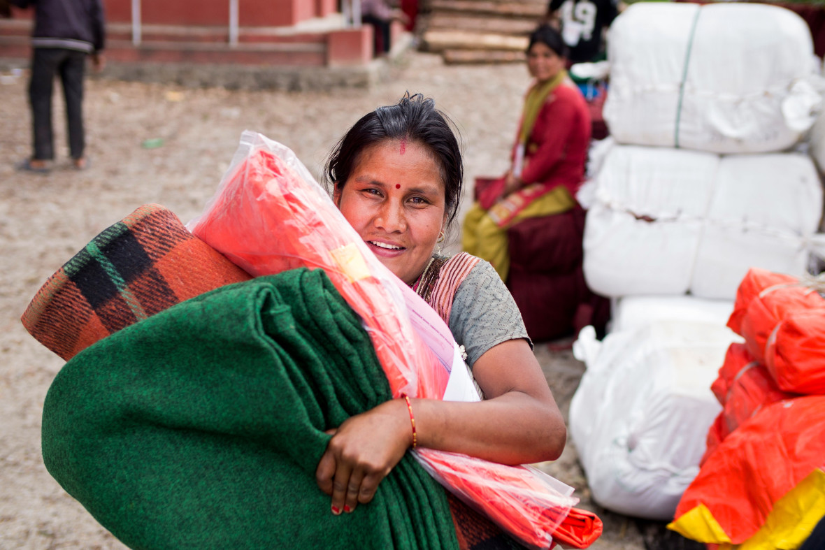 A woman collects blankets, a tarpaulin, and other necessities