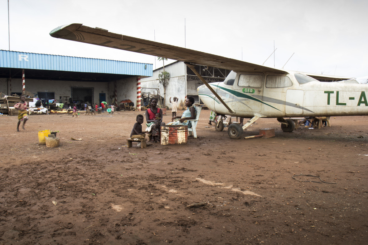 People sit underneath the shade of an abandoned airplane wing in the Mpoko displacement camp near the airport in Bangui.
