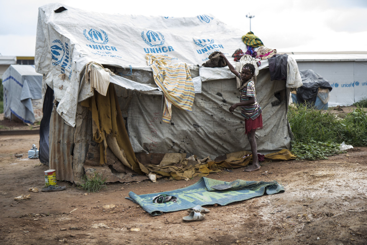 Child collects laundry drying on top of a makeshift shelter in the Mpoko displacement camp near the airport in Bangui.