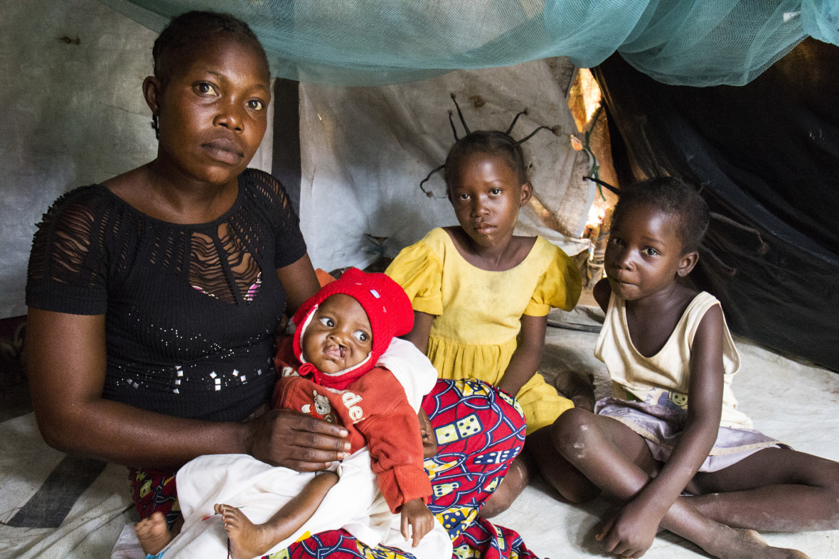 Gomokian Corine, 30, sits in her makeshift shelter in M'Poko displacement camp with her son, Grace-Dieu, eight months, and daughters Jennifer (left), eight, and Paula (right), six. Photo: Crystal Wells.