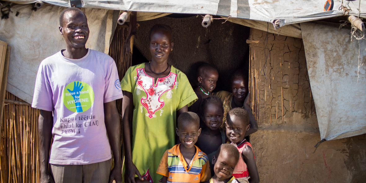 Simon Majiek with some of his children and extended family in front of their new shelter