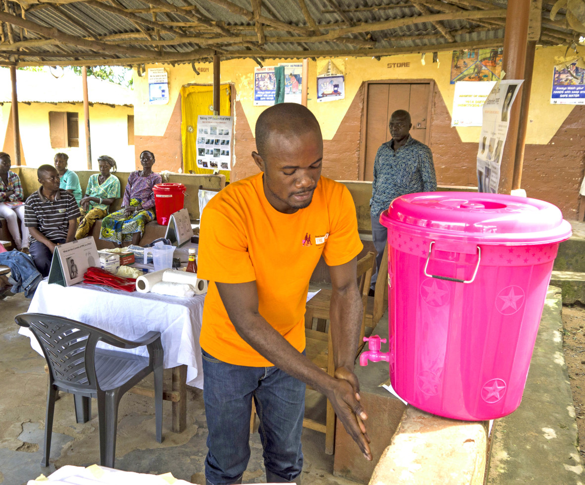 A man washes his hands using a Veronica Bucket.