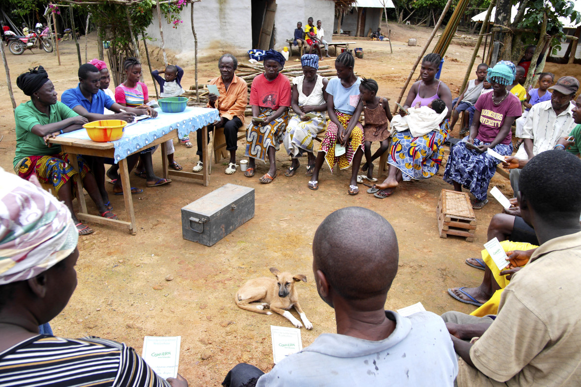 A village savings and loans group meets. In the center is their microfinance box.