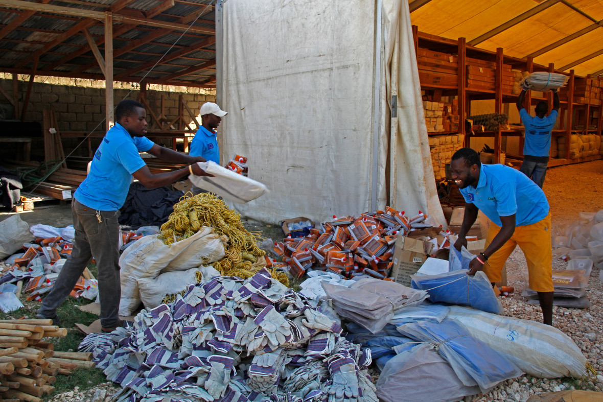 The Concern Worldwide warehouse in La Gonave. Concern Worldwide provided NFI's for families in need on La Gonave after Hurricane Matthew. Pictured: Gracia Jeanno and Ernso Romulus sort tarps for distribution. Photo: Kristin Myers