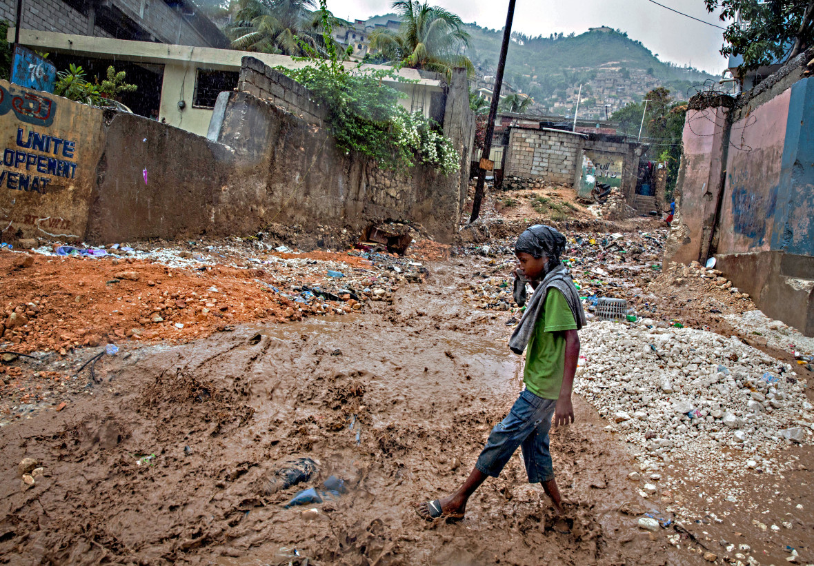 Child walks through flooded waters in Port-au-Prince