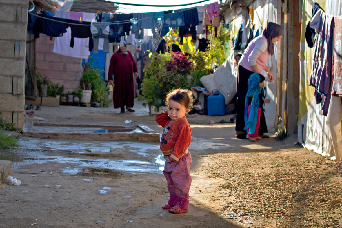 Syrian child stands alone in an informal settlement in Laebanon