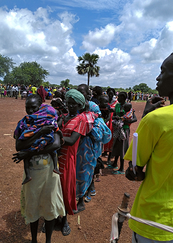 People wait in line for food in South Sudan