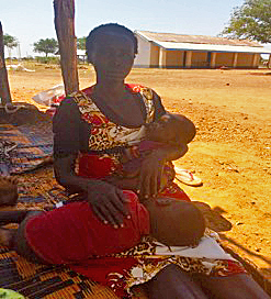 Mothers sits on blanket with children