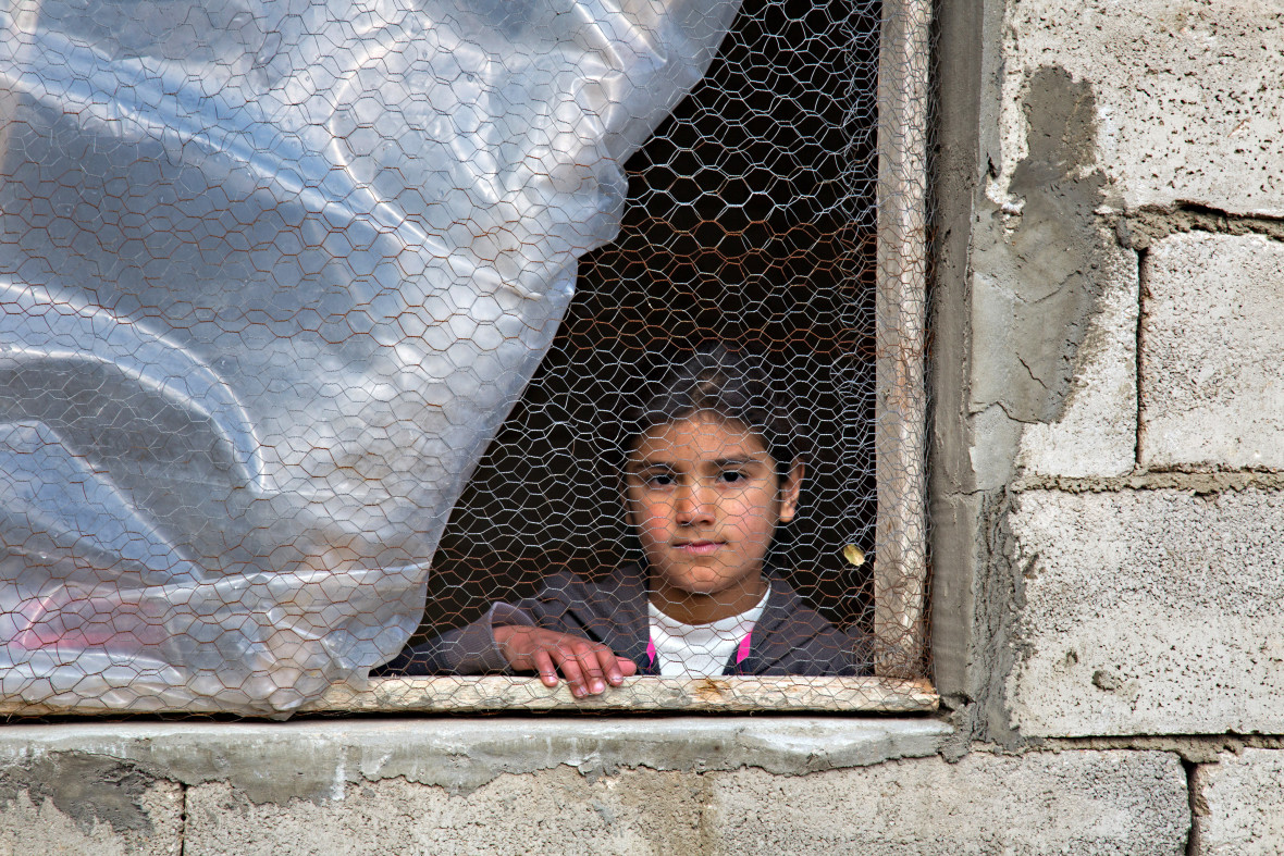 Syrian refugee Afaf, stands by the window