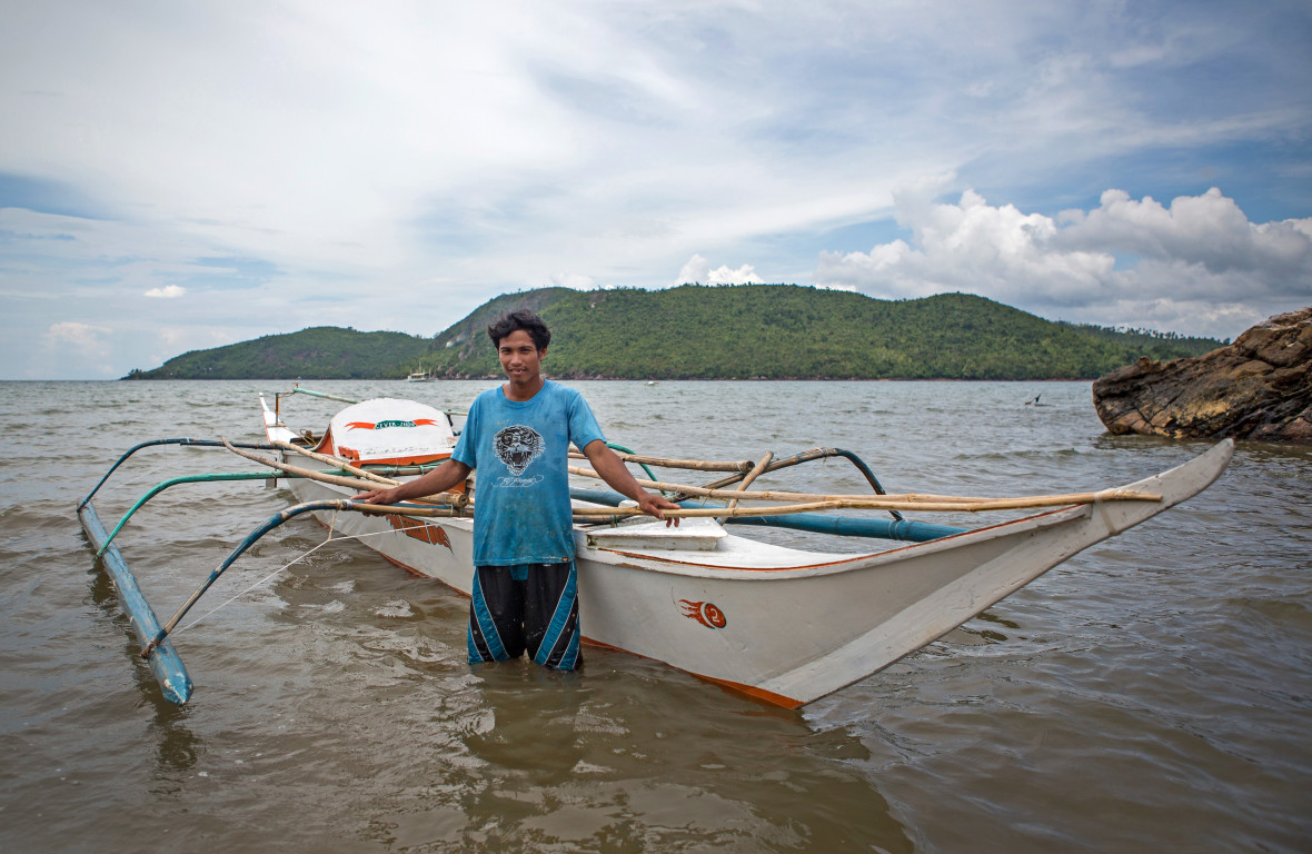 Nolito standing next to his new boat in the Philippines