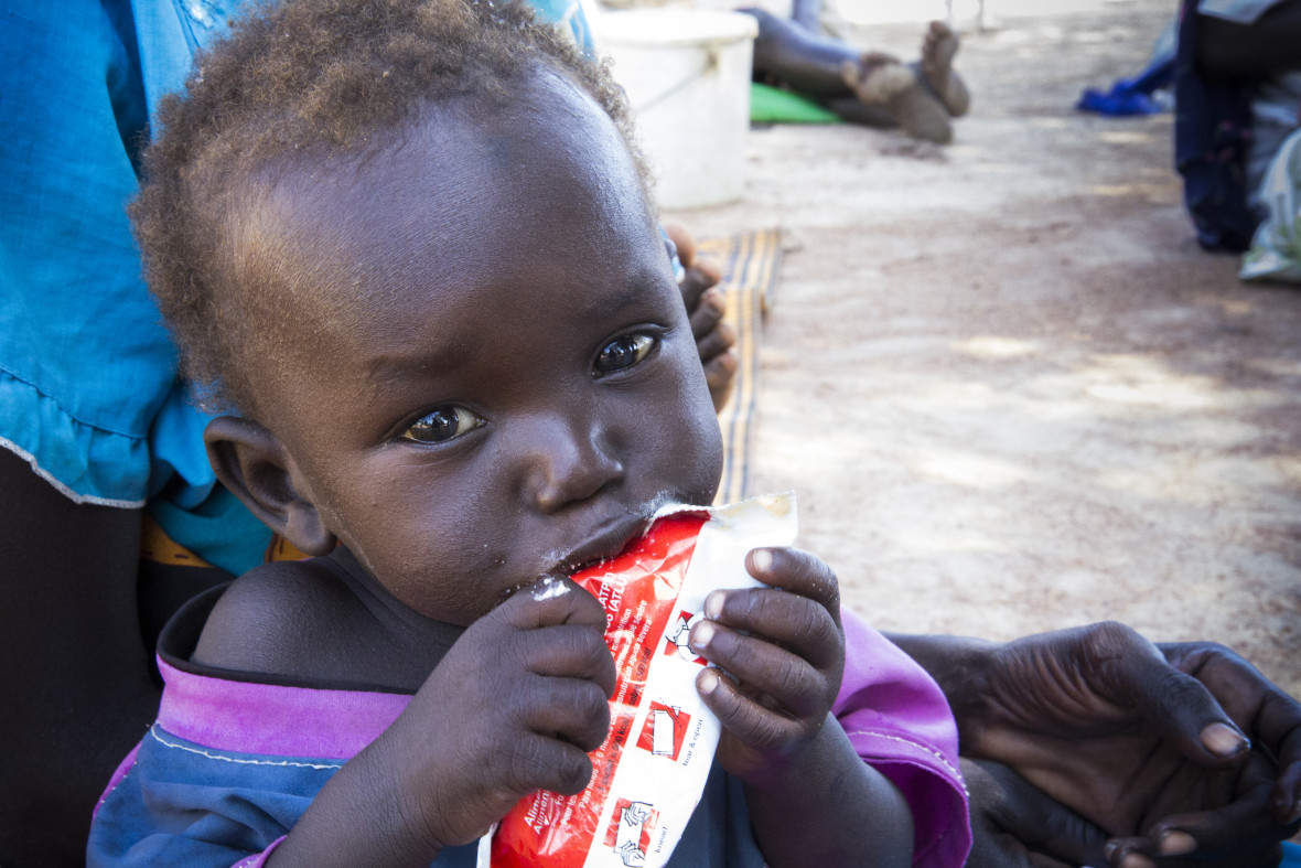 Small child eating from RUTF packet