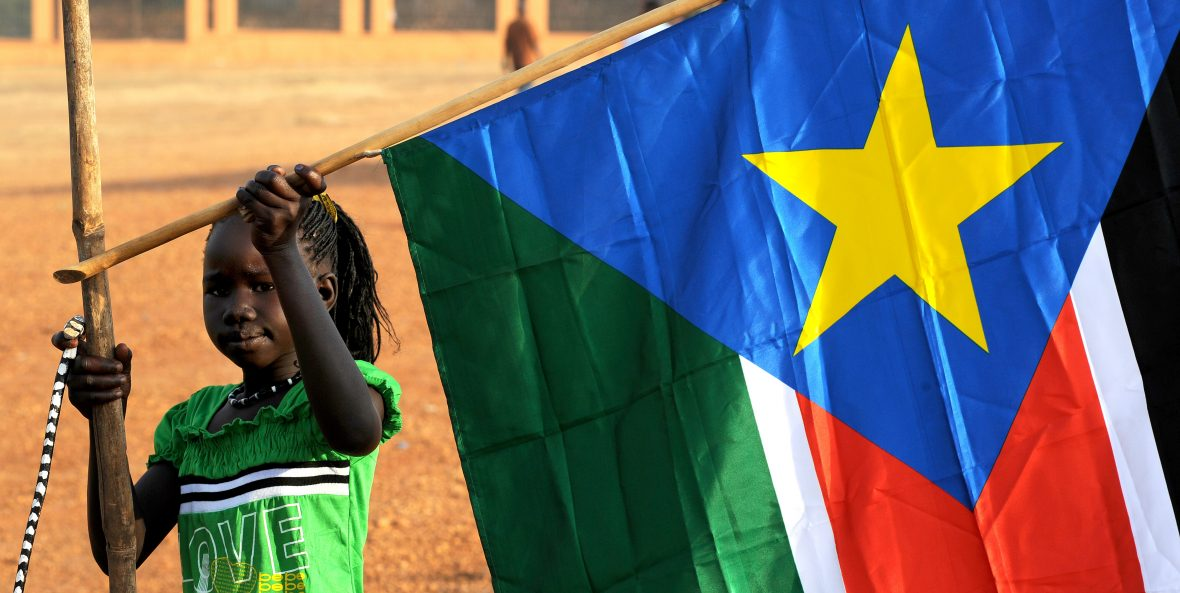 A young girl hangs the South Sudan flag following the country's independence referendum