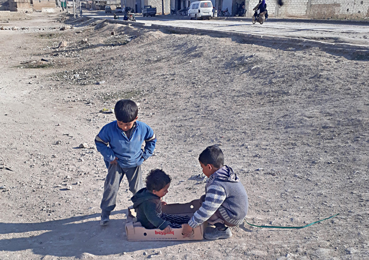 Syrian boys play with cardboard boxes in Syria